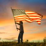 kid waving American flag at sunset